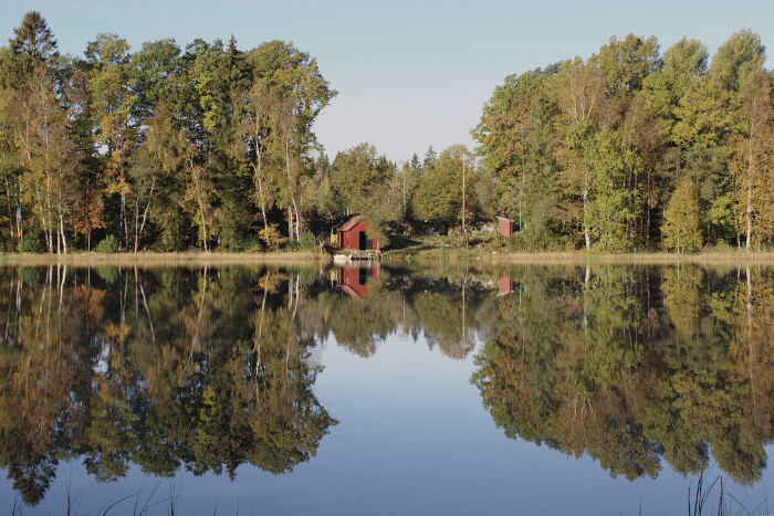 Still lake mirroring autumn trees and a small house