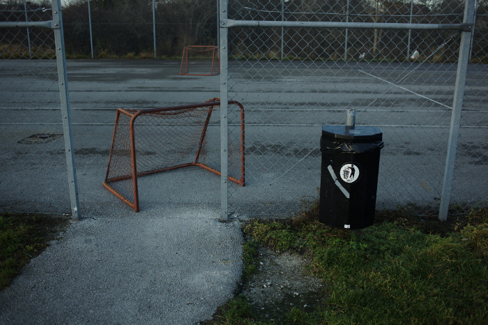 The entrance of an outside asphalt tennis court, with trash can and floorball goal.