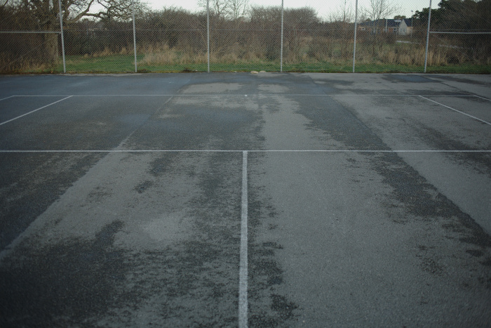 Asphalted tennis court, painted white lines on the ground and fence in the background.