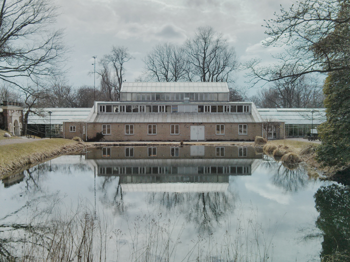 House being mirrored in the water. Also some trees.