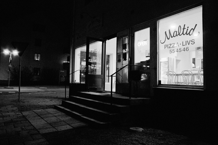 The pizza restaurant Måltid in the night, exterior and interior. Staircase leading up to the entrance.
