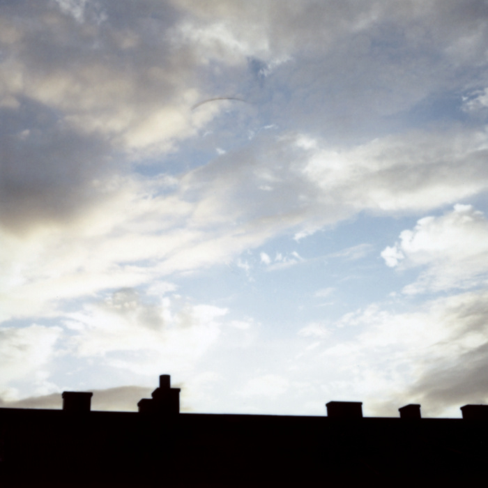Rooftop silhouette and beautiful blue sky with clouds.