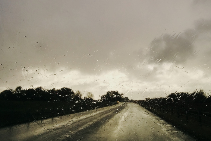 Rain drops on windscreen in focus. In the background, a road ahead, and rain clouds.