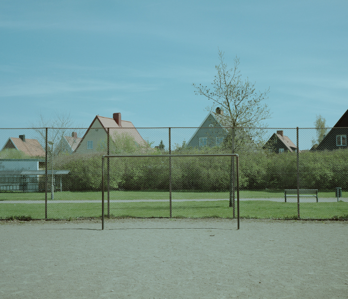 Gravel pitch, goal skeleton, and houses in the background.