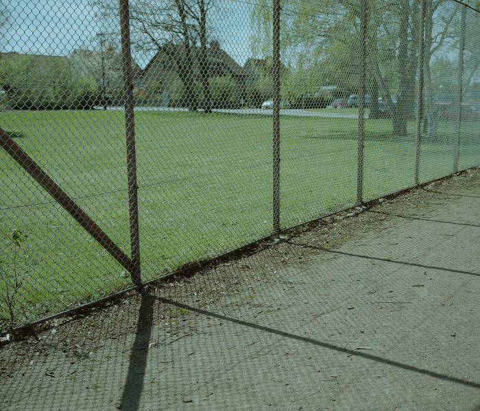 Fence and its shadows falling on gravel pitch like black sticks. Grass and some houses in the background.