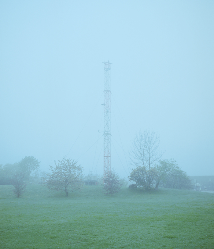 Radio mast partly covered in fog, grass in foreground.